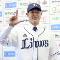 Tetsuya Utsumi poses for photos during his introductory news conference with the Seibu Lions on Friday in Tokorozawa, Saitama Prefecture. | KYODO