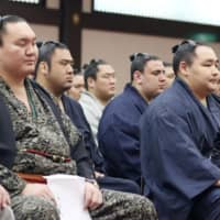 Sumo's yokozuna Hakuho (front left) Kakuryu (front center) and Kisenosato (front right) attend a workshop aimed at addressing violence against younger rikishi on Wednesday. | KYODO