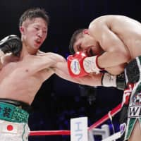 Takuma Inoue (left) lands a punch against Petch CP Freshmart during Sunday's WBC interim bantamweight title bout at Ota City General Gymnasium. | KYODO