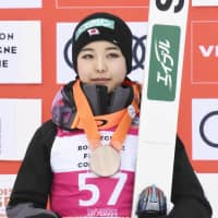 Sara Takanashi stands on the podium after placing third in Premanon, France | KYODO