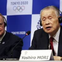 Tokyo 2020 President Yoshiro Mori (right) speaks as IOC inspection team head John Coates listens during a Dec. 5 news conference in Tokyo. The local organizing committee released the third version of its budget on Friday. | AP