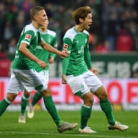 Bremen forward Yuya Osako (right) celebrates with teammates after scoring his team's first goal against Bayern on Saturday in Bremen, Germany. | AFP-JIJI