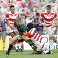 Kensuke Hatakeyama (3) tackles a South African player during their match at the 2015 Rugby World Cup on Sept. 19, 2015, in Brighton, England. | KYODO