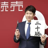 Giants pitcher Tomoyuki Sugano poses with a sign saying '20 wins' during a news conference on Monday.   KYODO