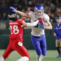 IBM wide receiver Yoshihito Oumi (right) stiff-arms Frontiers defensive back Yuki Ishii on Monday during the Japan X Bowl at Tokyo Dome. | KYODO