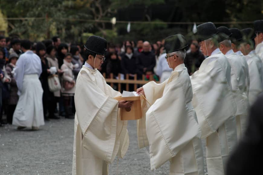 Priests carry the o-mamori to be blessed and burned.