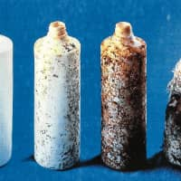 An eco-friendly, biodegradable polylactic acid, which is decomposed by microorganisms found in soil, is under development by Japanese researchers. The bottles pictured represent various stages of the plant-based plastic's decomposition. From left — zero weeks, two weeks, four weeks and six weeks. | JAPAN BIOPLASTICS ASSOCIATION
