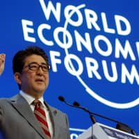 Prime Minister Shinzo Abe speaks at the World Economic Forum Annual Meeting in Davos, Switzerland, on Wednesday. | REUTERS