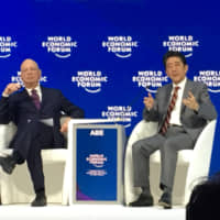Prime Minister Shinzo Abe speaks as Klaus Schwab, a noted economist and the founder and executive chairman of the World Economic Forum, looks on during the WEF annual meeting in Davos on Wednesday. | SAYURI DAIMON