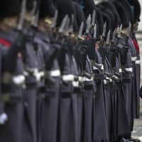 British Prime Minister Theresa May and Prime Minister Shinzo Abe review a military guard of honor in London on Thursday ahead of bilateral talks. | AP