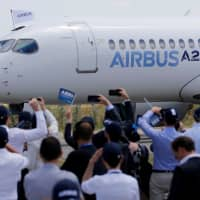 Airbus members celebrate the landing of an Airbus A220-300 aircraft during its presentation in Colomiers near Toulouse, France, last July. | REUTERS