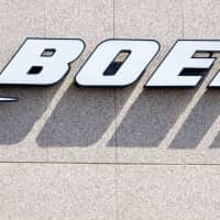 The Boeing logo is seen on a building in Crystal City, Virginia, in 2006. Boeing reported record commercial plane deliveries for the second straight year on Tuesday, although the figures missed the company's forecast. | AFP-JIJI