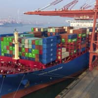 Containers are loaded onto a cargo ship at a port in Qingdao, in east China's Shandong province, on Friday. China's trade growth slowed in 2018 as a tariff battle with Washington heated up and global consumer demand weakened. | AP