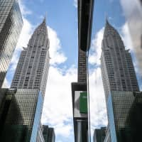 The Chrysler Building is seen reflected on a nearby building in New York on Wednesday. Abu Dhabi, majority owner of New York's Chrysler Building, is considering a sale of the landmark skyscraper, according to people with knowledge of the matter. | BLOOMBERG
