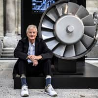 The founder of the Dyson company, designer James Dyson, poses next to the model of an engine during a photo session at a hotel in Paris in October. British electric appliance pioneer Dyson will switch headquarters to Singapore this year due to booming Asian demand but not because of Brexit, the company said Tuesday. | AFP-JIJI
