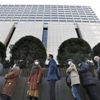 People wait in line Tuesday at the Tokyo District Court in hopes of getting one of  the 14 seats available to the public for an appearance by ousted Nissan chief Carlos Ghosn. | KYODO