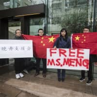 Supporters hold signs and Chinese flags outside the Supreme Court of British Columbia during the third day of a bail hearing for Meng Wanzhou, the chief financial officer of Huawei Technologies, in Vancouver, on Dec. 11. | AP