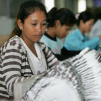 Women work at a Japanese plant in Cambodia. | KYODO