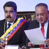 Diosdado Cabello, president of the National Constituent Assembly, speaks while Nicolas Maduro, Venezuela's president, listens during a state of the union address in Caracas on Monday. Maduro, speaking on state television, said the monthly minimum wage will rise to 18,000 bolivars. | BLOOMBERG
