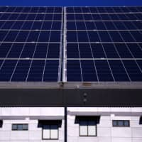 A solar array, a linked collection of solar panels, can be seen in front of a residential apartment block in the Sydney suburb of Chatswood in 2017.   REUTERS