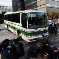 A police bus believed to be carrying ousted Nissan Motor Co. Chairman Carlos Ghosn leaves the Tokyo District Court on Tuesday. | REUTERS