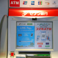 A customer shows a smartphone banking app in front of a Seven Bank ATM in October in Tokyo. The bank plans to add a facial recognition feature to the ATMs so people can instantly open bank accounts. | KYODO