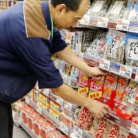 A shop employee arranges merchandise at a Tokyo supermarket. Government data released Friday show that households cut spending for the third straight month in November as unseasonably warm weather reduced the need for heating and winter clothing. | KYODO