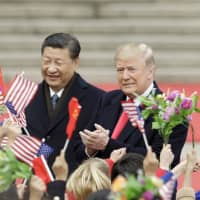 U.S. President Donald Trump and Chinese President Xi Jinping greet attendees waving American and Chinese flags during a welcoming ceremony outside the Great Hall of the People in Beijing in November 2017. | BLOOMBERG