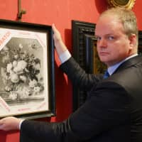A handout picture realeased by the Florence Museum Press Office on Tuesday shows the Florence Uffizi Galleries director Eike Schmidt posing with a copy of the 'Vase of Flowers' by Dutch painter Jan van Huysum, stolen from the Wehrmacht's Pitti Palace during World War II, in Florence, Italy. The Uffizi appealed to Berlin for help in retrieving the stolen 18th century Dutch painting from a German family. | FLORENCE MUSEUM PRESS OFFICE / VIA AFP-JIJI