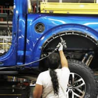 A United Auto Workers assemblyman works on a 2018 Ford F-150 truck being assembled at the Ford Rouge assembly plant in Dearborn, Michigan, in September. IHS Markit's latest monthly index should provide insight into the health of U.S. manufacturing. The financial information company's purchasing managers index, due out Wednesday, is a broad gauge of activity across the manufacturing sector. Economists project that December's reading dropped to 53.9. That would be the second monthly drop in for the index. | AP