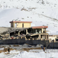 Afghan security forces inspect the site of a Taliban attack in the Maidan Wardak provincial capital of Maidan Shar, east of Kabul, on Monday.   AP
