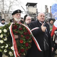 Polish far-right activists enter the former German Nazi death camp Auschwitz-Birkenau, on International Holocaust Remembrance Day in Oswiecim, Poland, Sunday. | AP