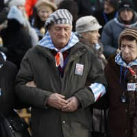 Survivors of Auschwitz arrive at the International Monument to the Victims of Fascism at the former Nazi German concentration and extermination camp KL Auschwitz II-Birkenau walk to place candles on International Holocaust Remembrance Day in Oswiecim, Poland, Sunday. | AP