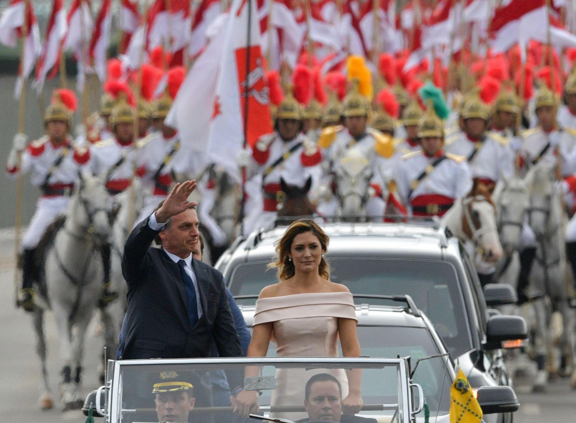 Brazilian President-elect Jair Bolsonaro waves at the crowd next to his wife, Michelle Bolsonaro, as the presidential convoy heads to the National Congress for his swearing-in ceremony, in Brasilia Tuesday. Bolsonaro takes office with promises to radically change the path taken by Latin America's biggest country by trashing decades of center-left policies. | AFP-JIJI