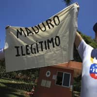 Venezuelan citizens living in Brazil hold a piece of cloth with a message that reads in Spanish 'Maduro illegitimate' during a protest over the government of President Nicolas Maduro, outside the Venezuelan Embassy in Brasilia Wednesday, . | AP