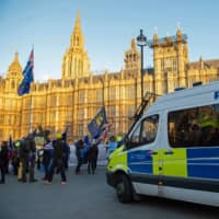 British police officers wait in their van as anti-Brexit activists demonstrate opposite the Houses of Parliament in London on Tuesday. | AFP-JIJI