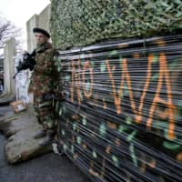 Dressed as a British Army soldier, a member of the anti-Brexit campaign group 'Border Communities Against Brexit' poses with a wall installed on a road crossing the border between Northern Ireland and the Republic of Ireland during a demonstration in Newry, Northern Ireland, on Saturday. | AFP-JIJI