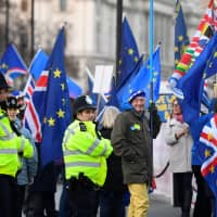 Anti-Brexit protesters demonstrate outside the Houses of Parliament in London Tuesday. | REUTERS