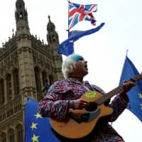 An anti-Brexit protester performs outside the Houses of Parliament after Prime Minister Theresa May's Brexit deal was rejected, in London Wednesday. | REUTERS