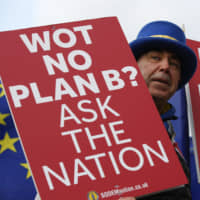 Steve Bray, an anti-Brexit demonstrator, holds placards during ongoing pro- and anti-Brexit protests outside the Houses of Parliament in London on Tuesday. The U.K.'s main opposition party is backing a plan that could open the door to a second European Union referendum, bringing the possibility of stopping Brexit a step closer. | BLOOMBERG