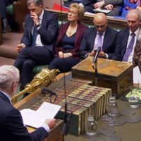 A video grab from TV footage shows Britain's Prime Minister Theresa May listening as opposition Labour party leader Jeremy Corbyn responds to her statement on changes to her Brexit withdrawal agreement on Monday. | PARLIAMENTARY RECORDING UNIT / VIA AFP-JIJI