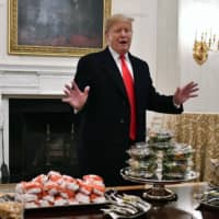 U.S. President Donald Trump looks over tables of fast food for the the college football playoff champion Clemson Tigers in the State Dining Room of the White House in Washington on Monday. | BRAD MILLS / USA TODAY / VIA REUTERS