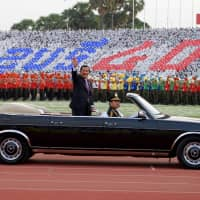 Cambodian Prime Minister Hun Sen, president of the Cambodian People's Party, waves during the CPP ceremony to mark the 40th anniversary of the fall of the Khmer Rouge regime at the National Olympic Stadium in Phnom Penh on Jan. 7. | AFP-JIJI