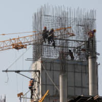 Laborers are seen working on a construction site in Phnom Penh on Tuesday. | REUTERS
