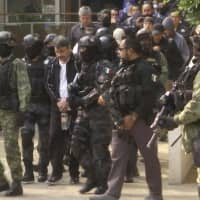 Damaso Lopez, a leader in Mexico's Sinaloa drug cartel, is escorted by police after his capture at an upscale apartment building in Mexico City in 2017. Lopez testified Wednesday at the U.S. trial of the Mexican drug lord known as El Chapo, implicating the kingpin's wife in his 2015 prison escape. | AP