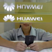 A sales assistant in China looks at her mobile phone as she waits for customers behind a counter at a Huawei booth in Wuhan, Hubei province, in October 2012. | REUTERS