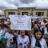 Demonstrators hold a placard reading 'Colombians, Let's not allow the war to polarize our country anymore' as they gather at Bolivar square in Bogota to demonstrate against terrorism, in repudiation of the police academy rcar bombing, and in support of the victims and their relatives, on Sunday. | AFP-JIJI