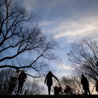 A woman walks her dogs in Central Park at sunset on Saturday in New York City. | AFP-JIJI