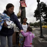 Venezuelan migrants arrive to a street corner to beg for money in Quito last November. Ecuador's government announced on Monday that it will require Venezuelan migrants who want to enter Ecuador to show their judicial record.   AP