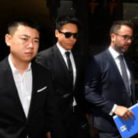 Chinese actor Gao Yunxiang (center) leaves the Downing Centre court in Sydney on Friday. | AAP /VIA REUTERS